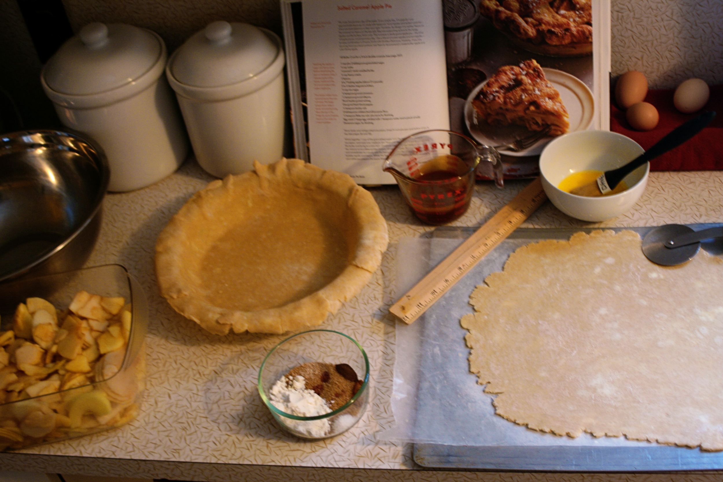 Here's aview of what I had ready for myself on day two thanks to day one's prep: apples, sliced and mixed with lemon and sugar; sugar-spice mixture; caramel, measured and ready to pour; pie dough that had been rolled out, halfleft on a sheet tray and popped into the freezer (only spot it fit) and one placed in the pie pan (kept in the fridge).