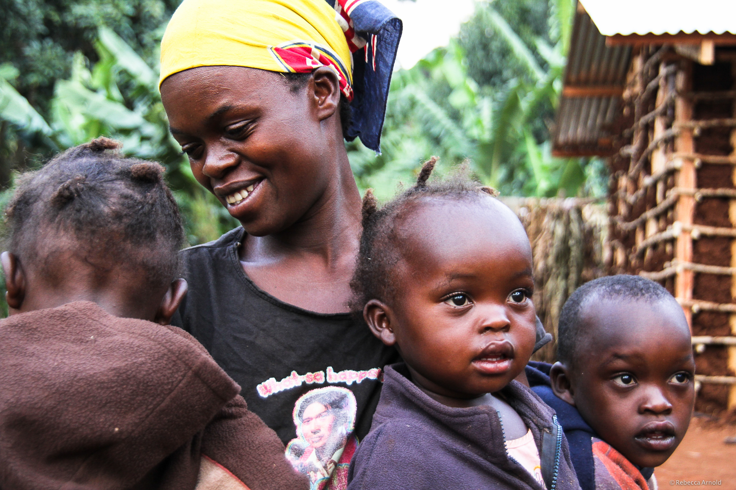 Kapchorwa, Uganda. Her increased crop yield means a new house being built behind her for her four kids.