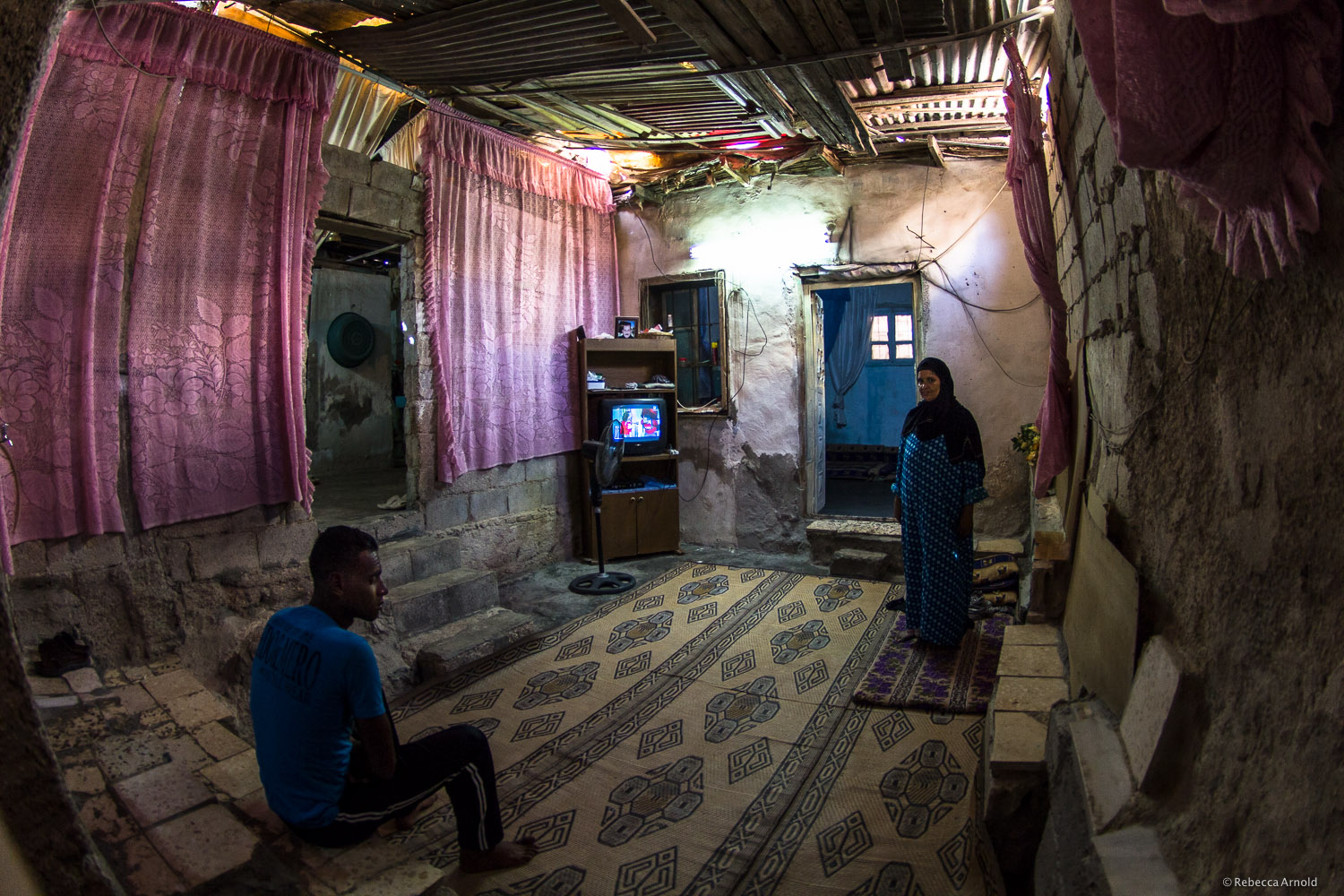 Syrian refugee mother and son, making a home in abandoned house  with no roof. Zarqa, Jordan