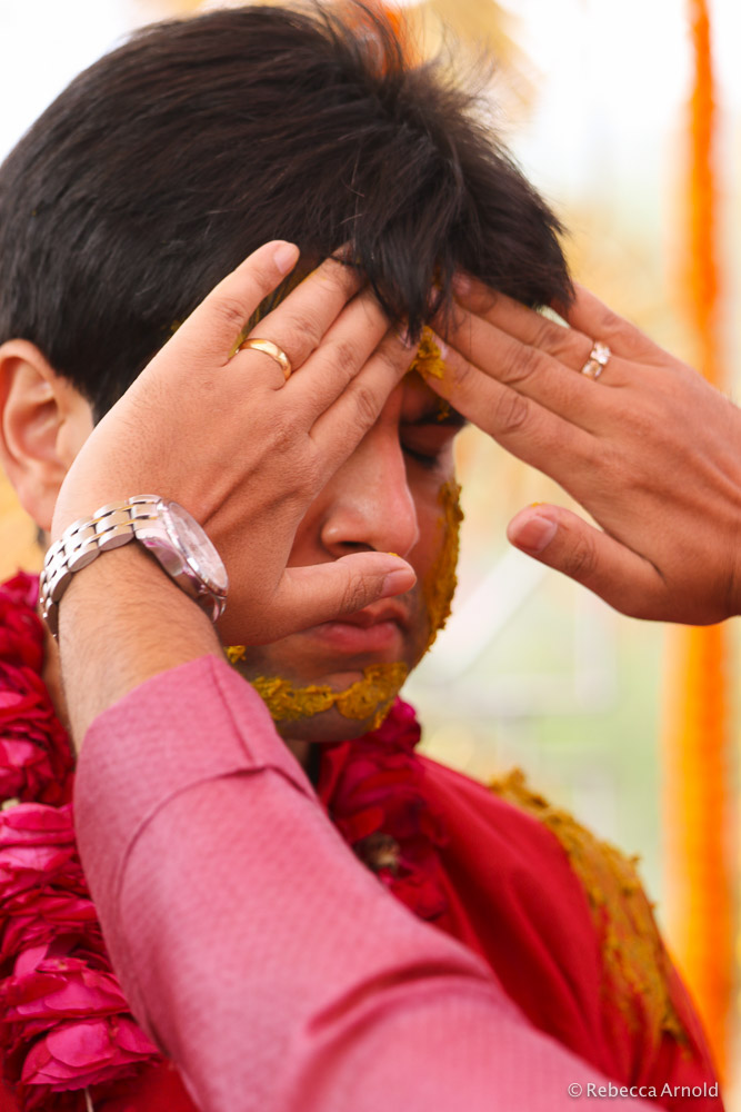 Haldi; the groom, Rajat, gets turmeric paste put on his face for good luck and health.