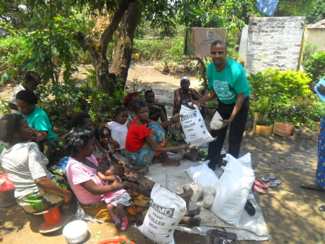 Stanley giving maelie meal and beans to Sharon Musonda in Buchi community