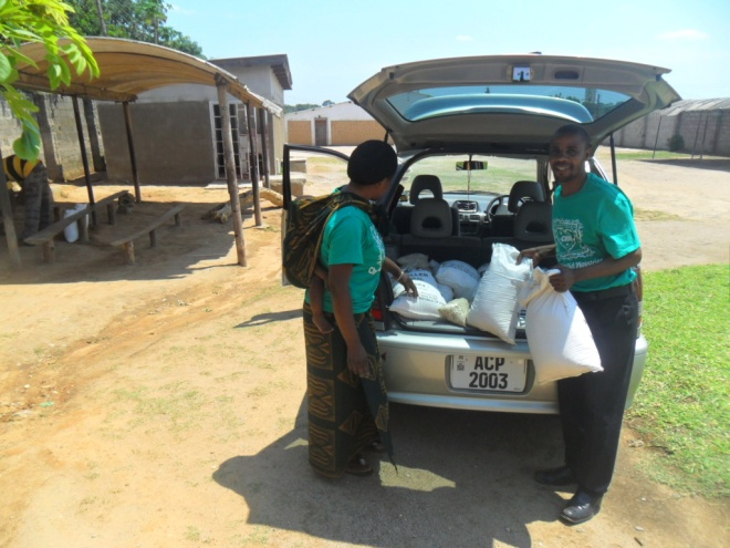Stanley and Bernadette offloading mealie meal and beans from a hired vehicle in readiness for food distribution to TB clients in kamatipa community