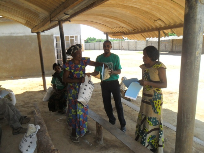 Stanley and Mary Kampyongo, kamatipa community volunteer giving melie meal and beans to Jenifer Mukwabila