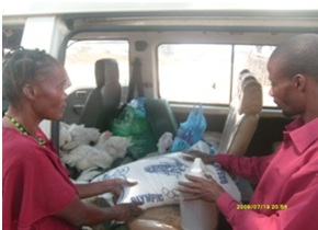 Catherine and Stanley Mulenga offloading mealie meal chickens cooking oil beans and some clothes in readiness for distribution to the patients in St. Anthony community