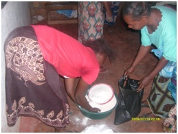 Catharine's first born daughter (in red) sharing mealie meal to Christine Buleti out TB and HIV/AIDS patient in St. Anthony community