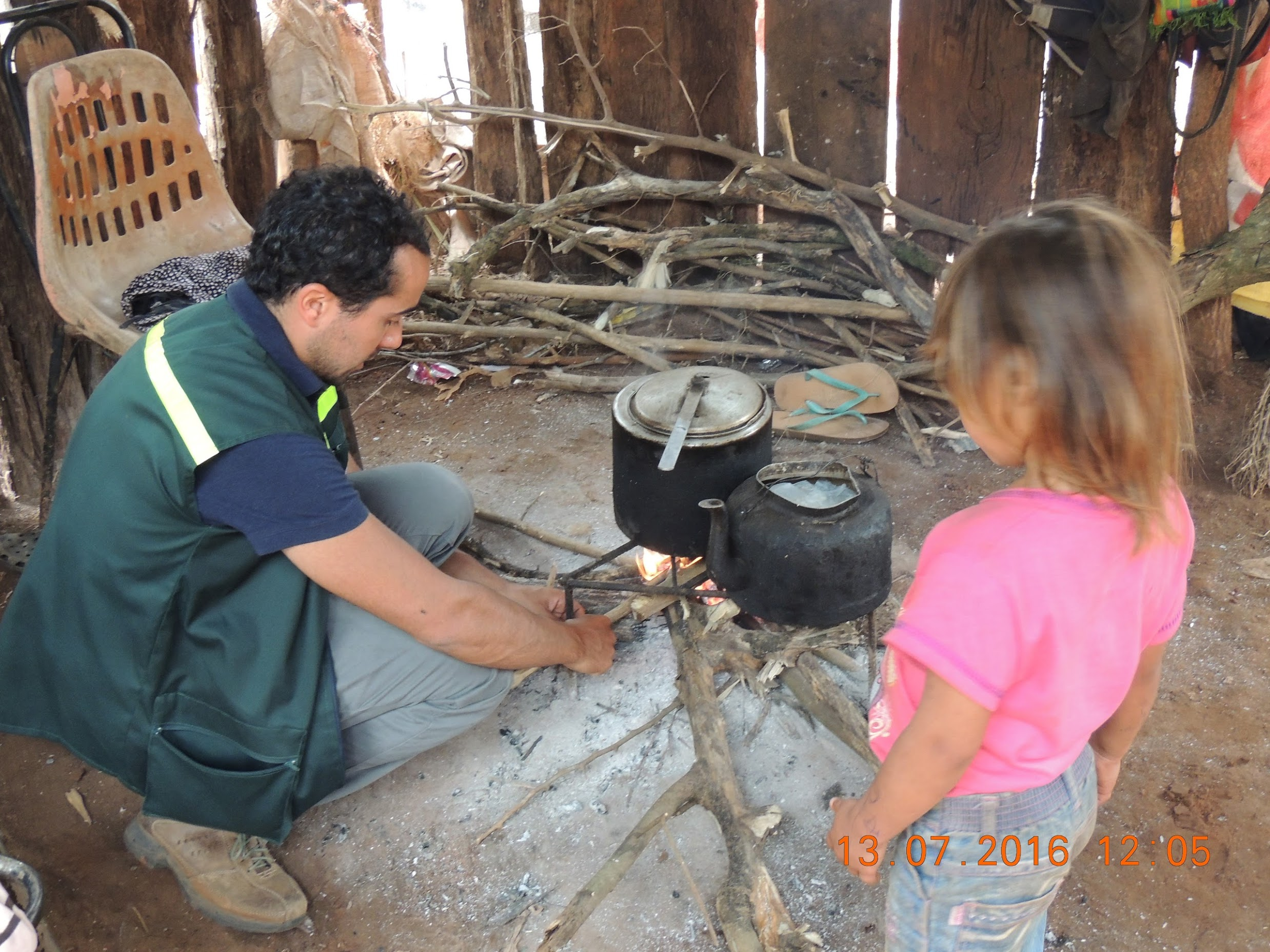 A kid looking  Matias Tagle  (GHE 17) installing a stove monitor in Paraguay.