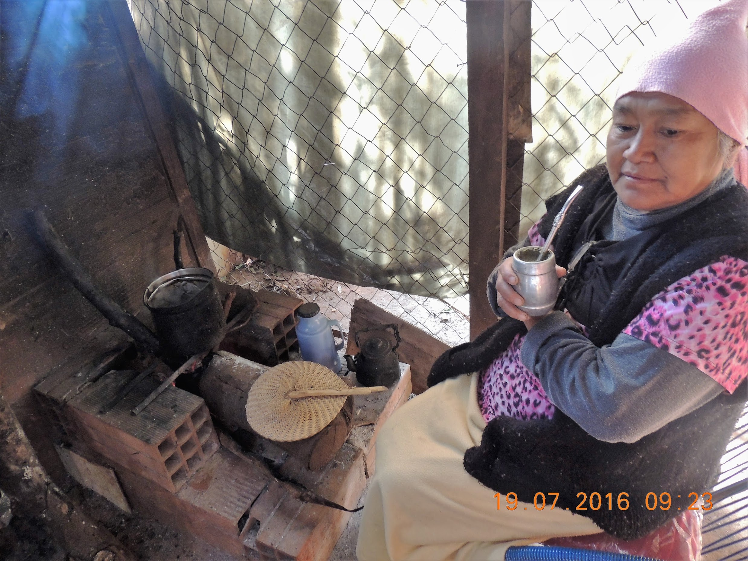 A woman in Paraguay burning wood and drinking  mate.
