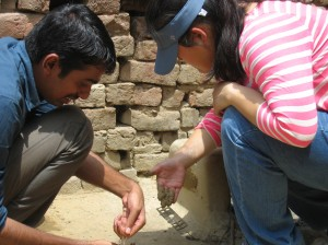 Jenny Eav  (GHE '14) and a colleague from INCLEN placing stove use monitors on a traditional mud chullah. Jenny's research project focuses on evaluating a new platform for monitoring stove use.