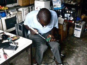 Computer repairman soldering a circuit board on his lap — from  Georgia Green 's (GHE '11) fieldwork on electronic waste workers in Abidjan, Côte d'Ivoire