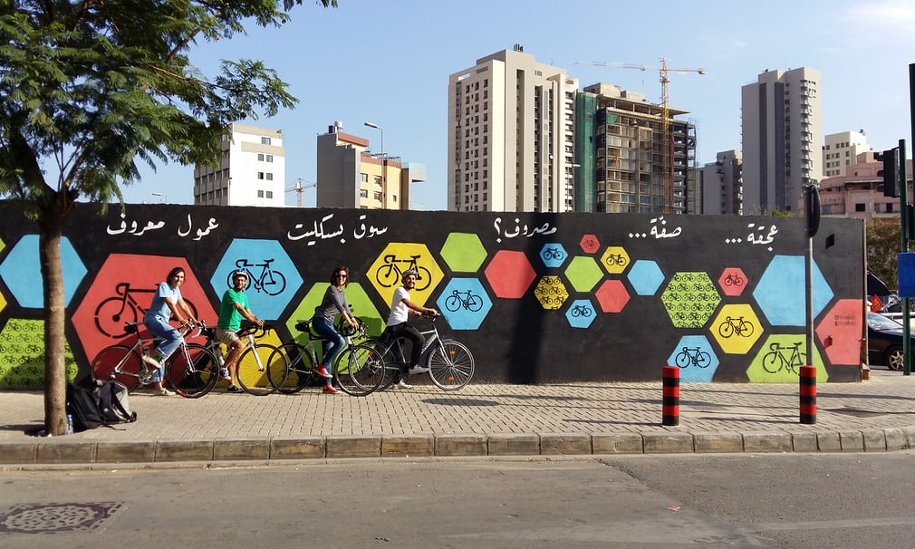"Members of The Chain Effect next to one of their 2016 murals in Beirut which reads ""Traffic.. parking.. expenses.. ride a bicycle instead please!"". Each painting is eye catching and encouraging with words that rhyme in Lebanese Arabic.   Source:  https://www.theguardian.com/cities/gallery/2017/jun/15/beirut-bike-street-art-chain-effect-in-pictures"