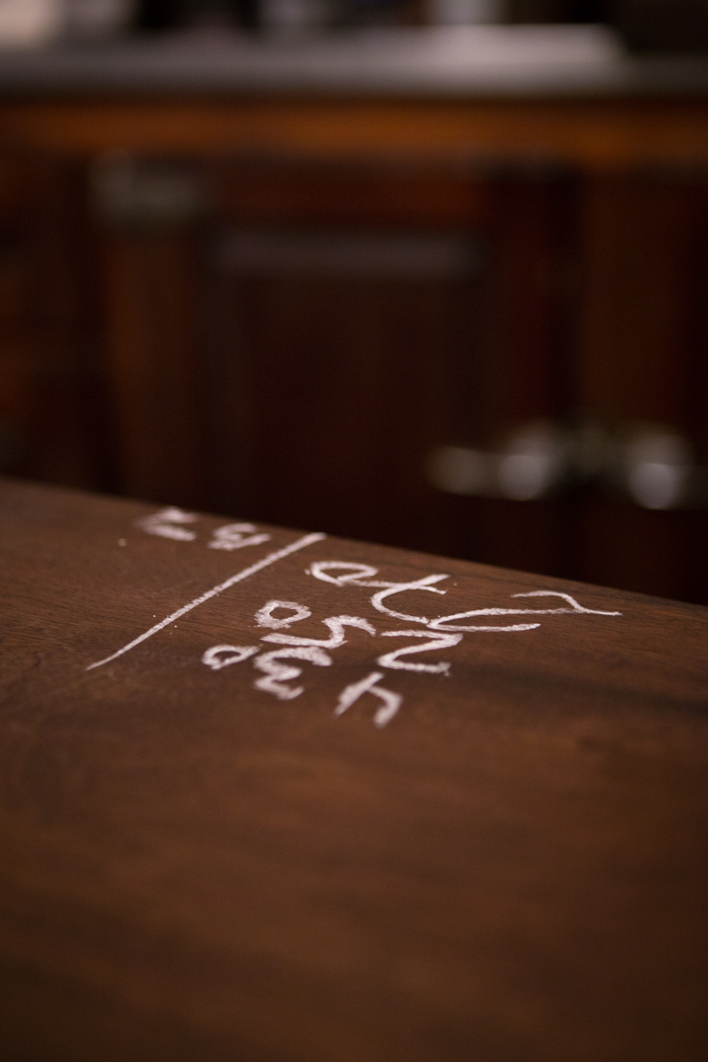 Each tab is tallied by chalk on the wooden bar surface