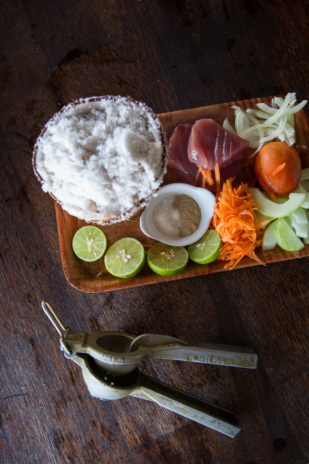 Simple ingredients for poisson cru: fresh coconut, lime, salt, pepper, fresh tuna, carrots, cucumber, onion, tomato