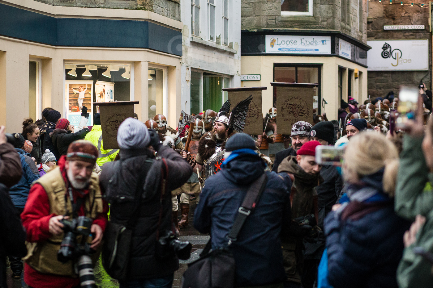 The press throng around the Jarl's Squad as they come through the centre of town.