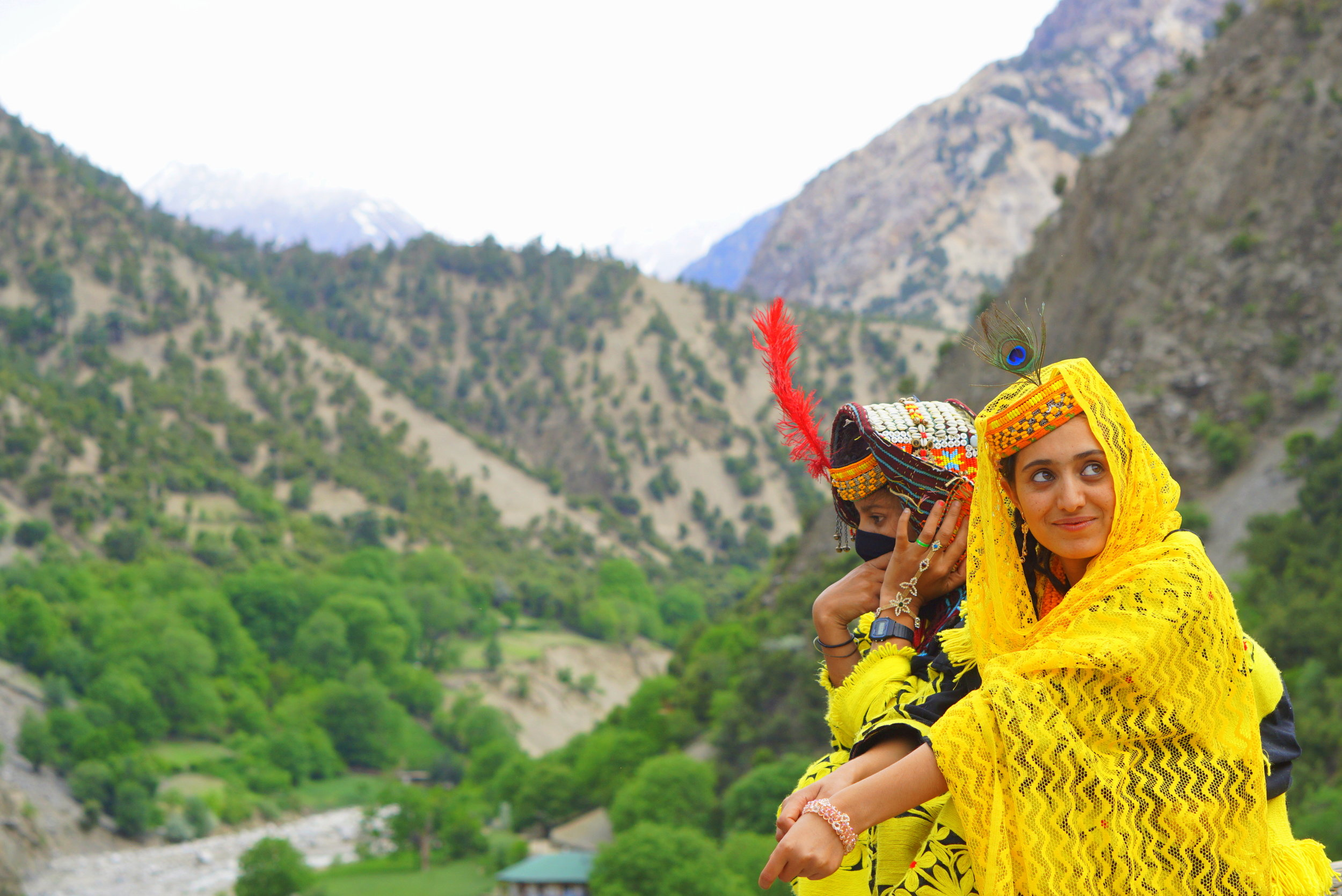 Two Kalashi girls overlook the view in Bamburat village during the annual Chilam Joshi festival in the Hindu Kush region (Omer Imran)