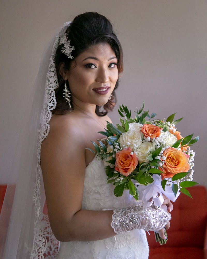 Closeup of bride with bouquet by window