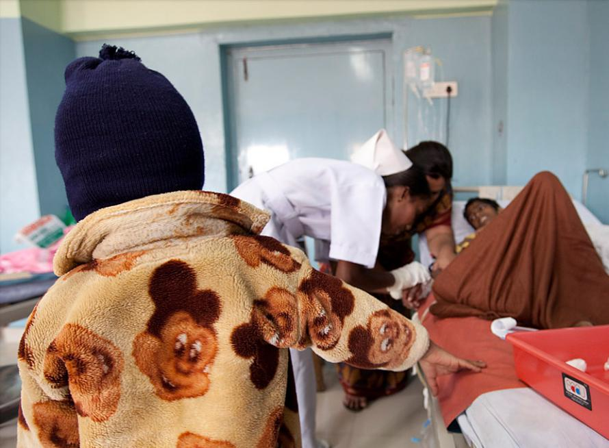 A fellow patients watches paediatric nurses administer medication to Suresh to combat the nausea he experienced.