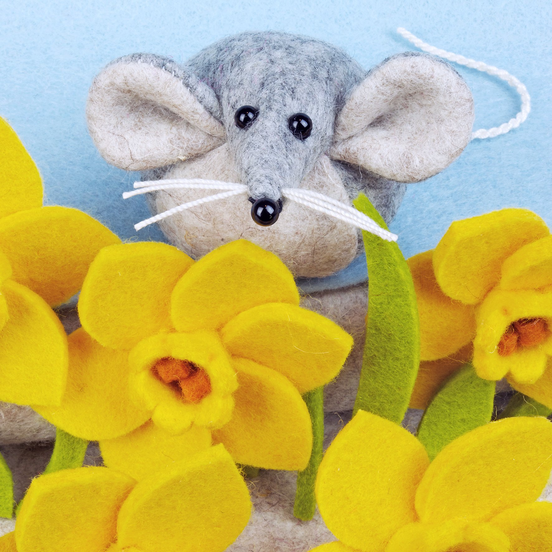 Marie the Mouse with daffodils in the Spring. Handmade from wool felt.