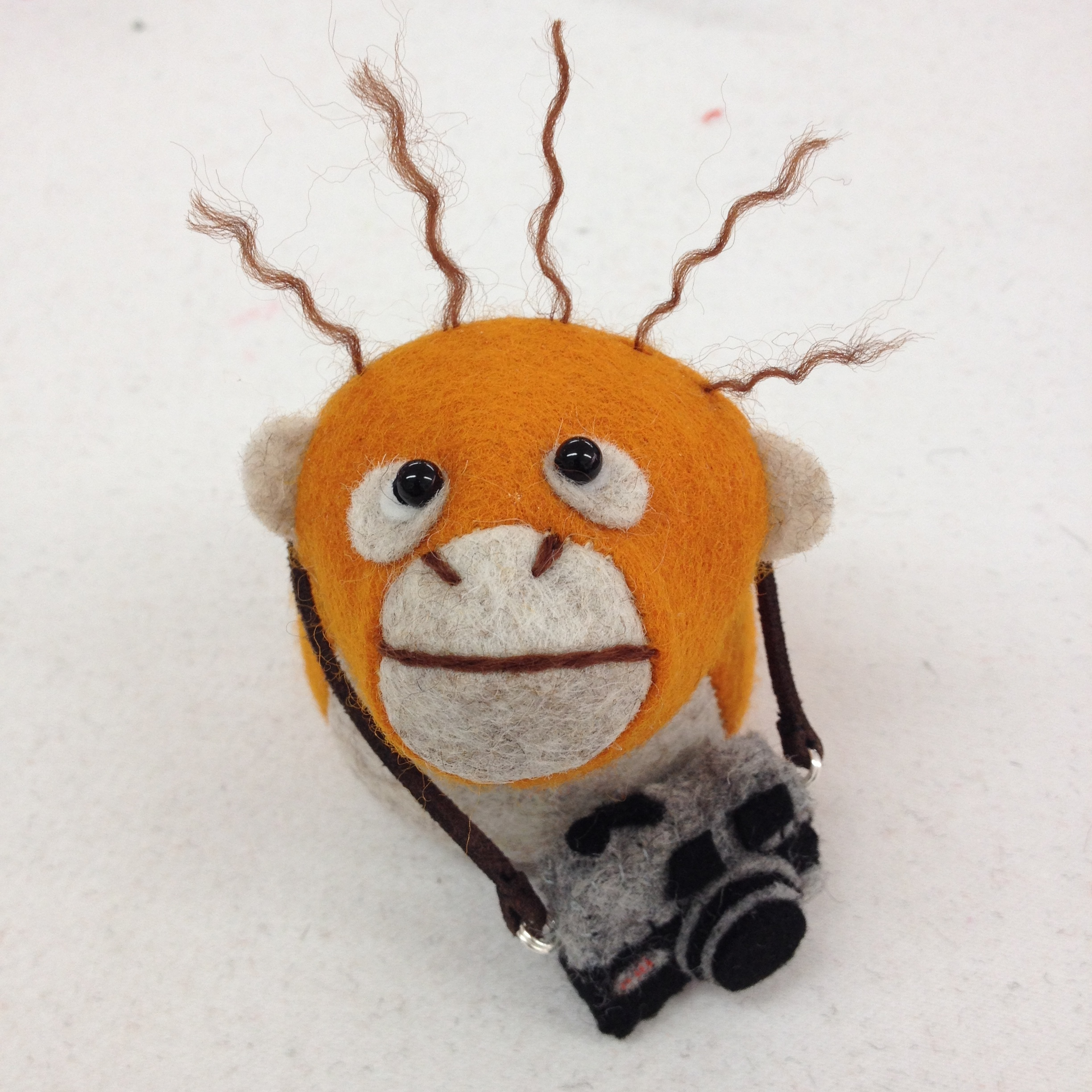 Bilberry Woods character Oscar the Orangutan with a miniature felt camera by Laura Mirjami | Mirjami Design