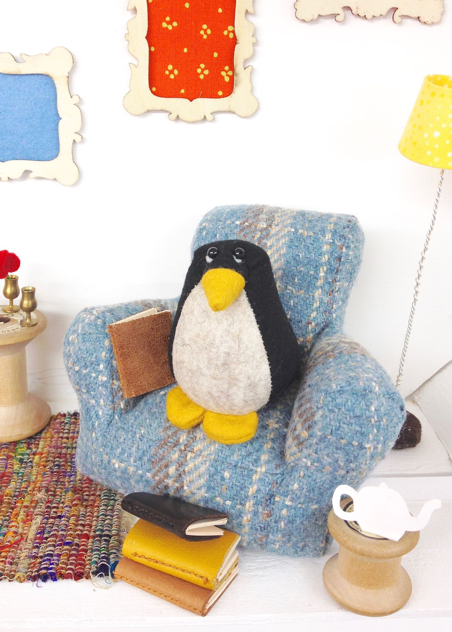 Bilberry Woods character Pedro the Penguin sitting on his tweed chair reading books | Handmade by Laura Mirjami | Mirjami Design..jpg