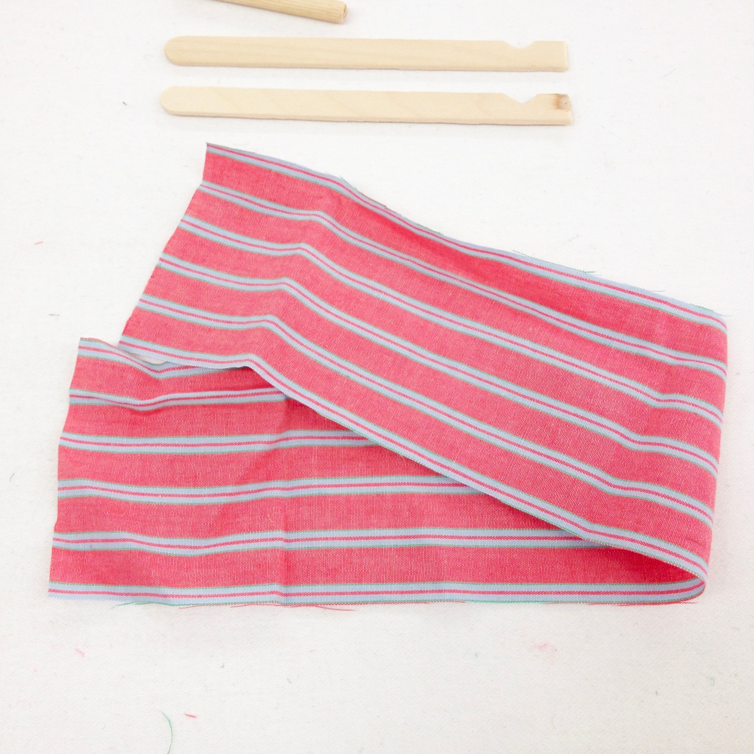 Cut a long strip of fabric, fold over the right side and sew. Leave gaps for dowels.