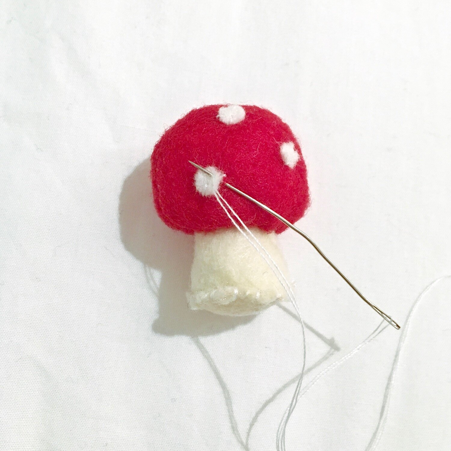 Cut out small felt spots or use a leather hole punch and Add the spots either by stitching or with glue.