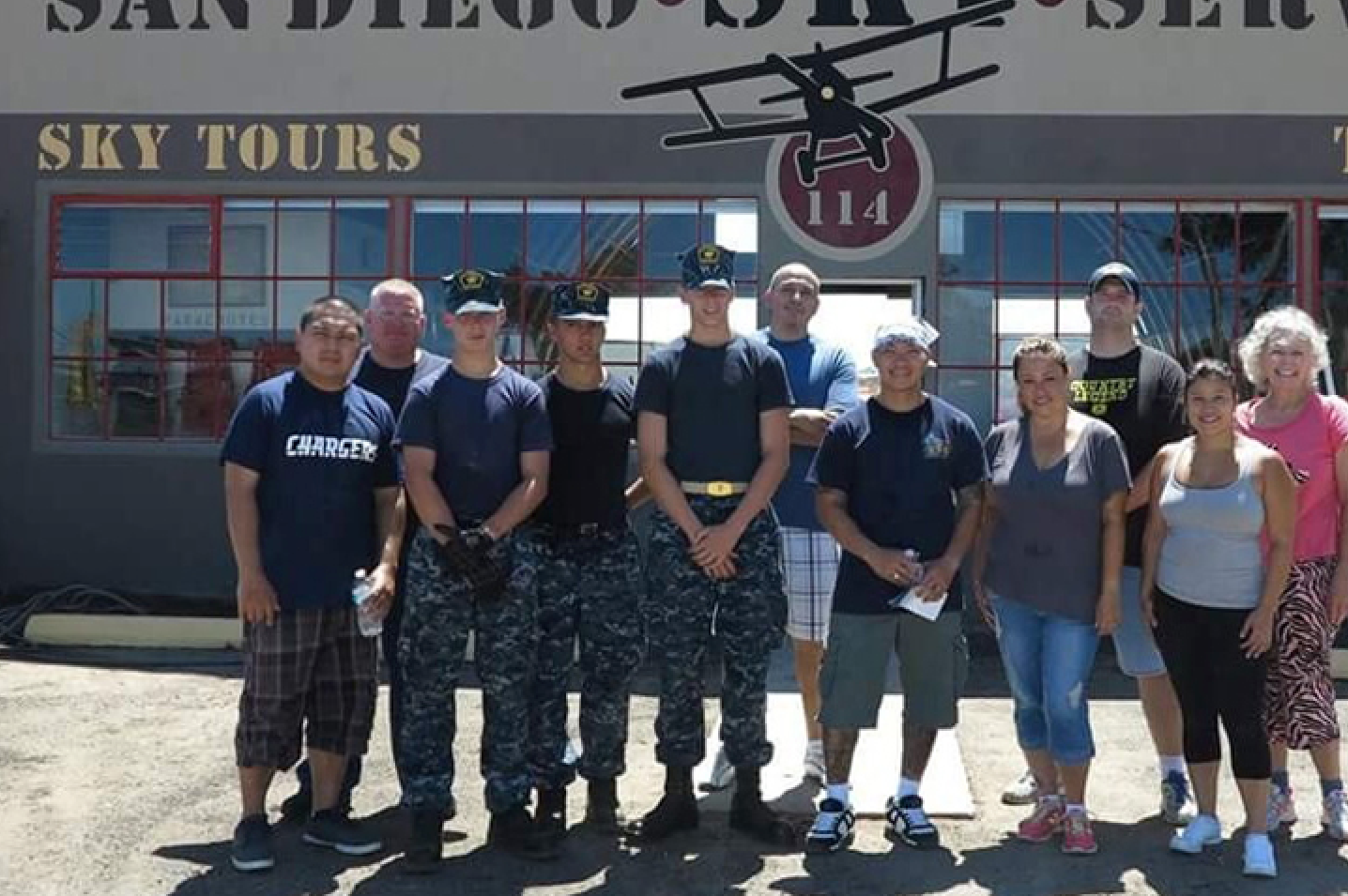Navy personnel participating in aviation events at old Sky Tours hangar.