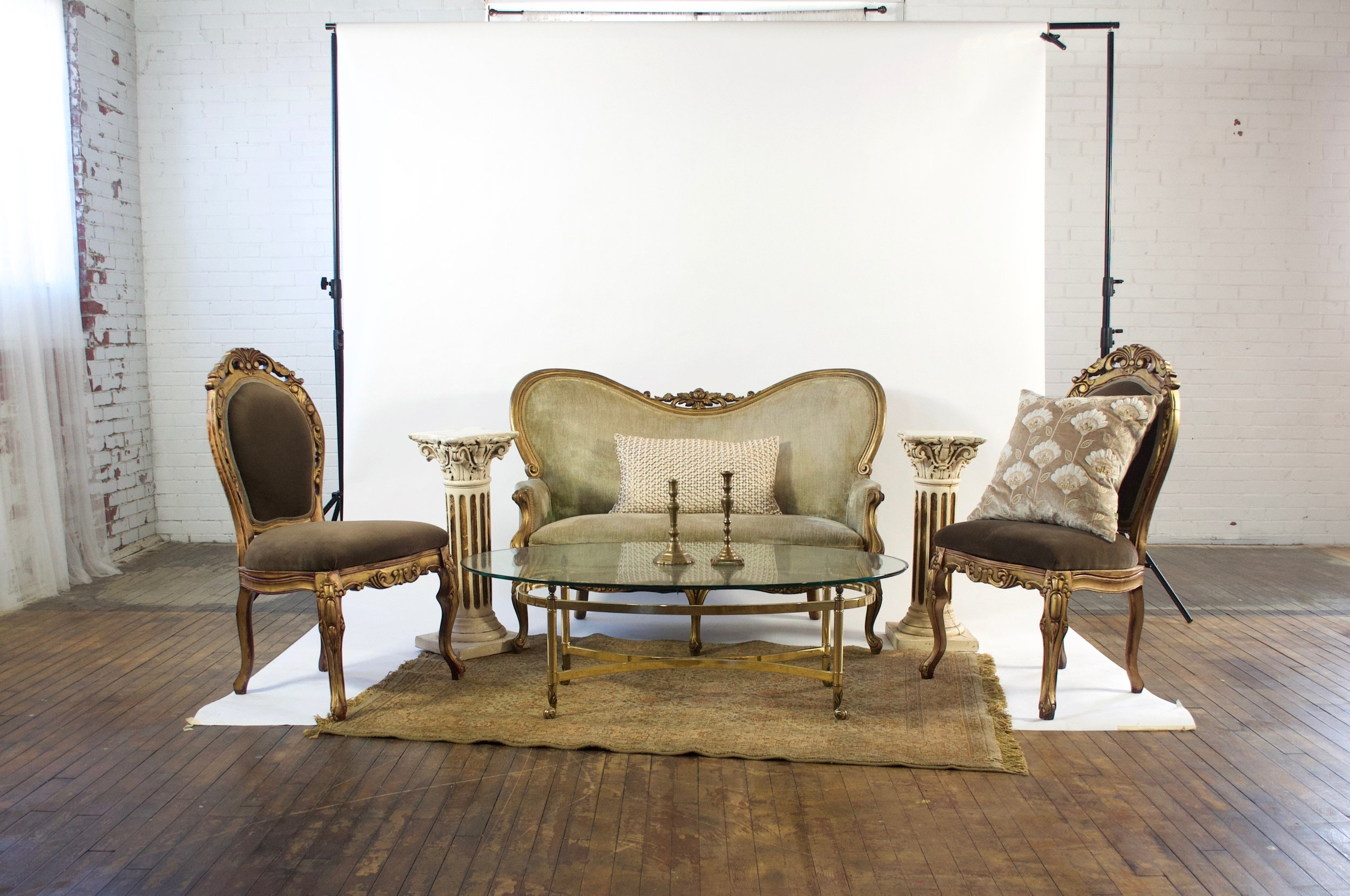 Goldie and Duren Demi - featuring beige rug, oval glass and gold table, and twin pedestals