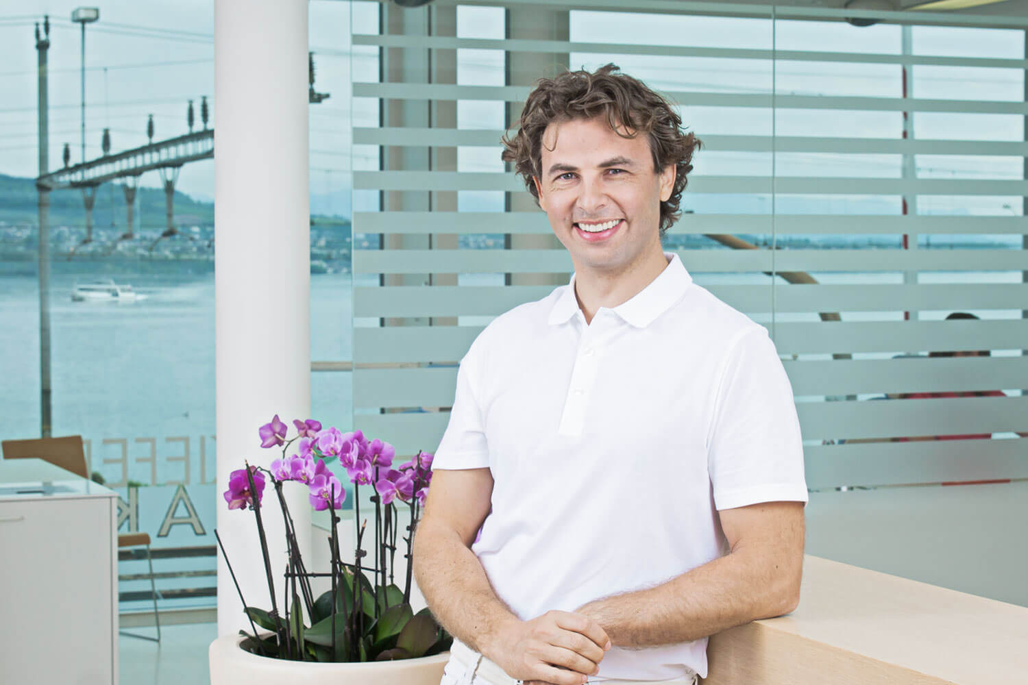 Corporate portrait of orthodontist Dr. med. dent. Alexander Dudic (PHD) in front of the treatment room overlooking lake Zurich.