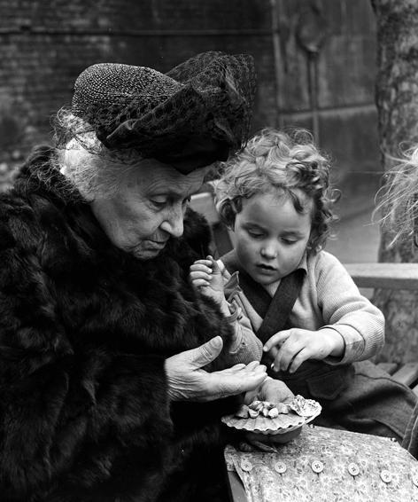 Dr. Maria Montessori is working alongside a child in a Children's House outdoor environment.  The Button Dressing Frame in Dr. Montessori's lap is a  Practical Life  material used to support and encourage the child's care of herself by building her hand-eye coordination, concentration, independence and order.