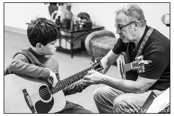 Music teacher Jim Svendsen helping young guitar student learn finger placement on the frets.