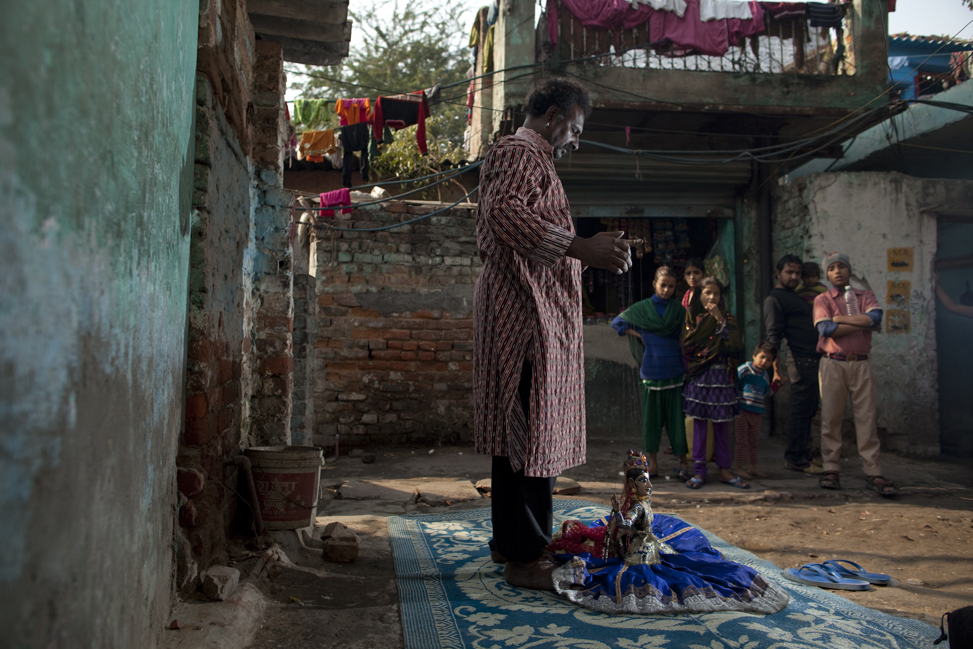 Puran Bhatt practices with a traditional dancer puppet in a back alley of Kathputli.