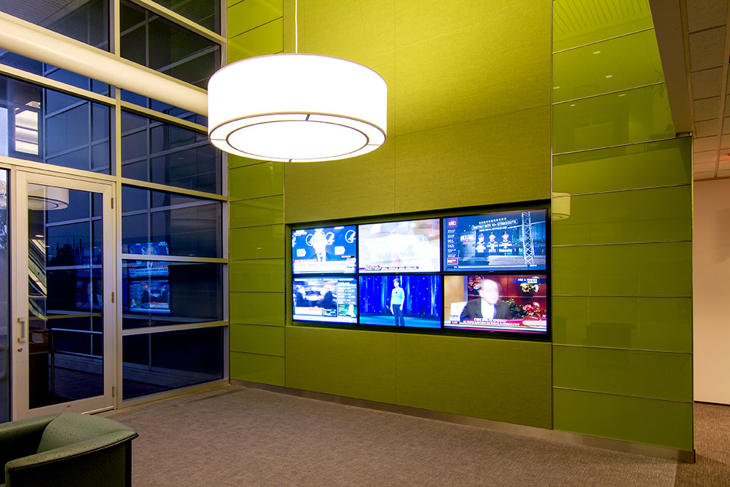 This oversized Level 3 Elevator lobby serves also as an open collaborative meeting area for tenants and visitors to the building.  The Video grid wall is set in fabric panels with back-painted glass accents and stainless base.