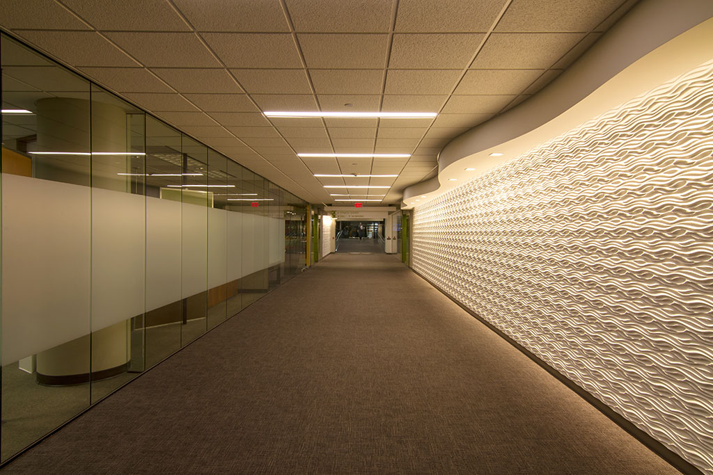 This is the main entry corridor on Level 3 from the main staff parking garage.  The generous width of 14' allowed accenting the length with new textured wall panels, the wave header and specialty lighting.