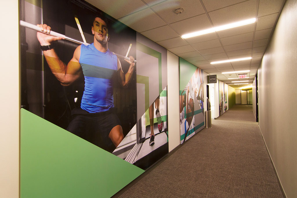 Large scale photo and graphic panels bring the eye of the viewer down a connecting corridor to the new workout facility.