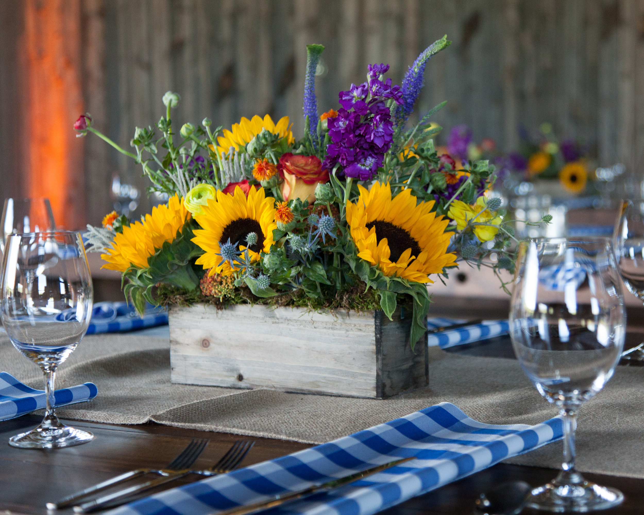 """We recently had a great opportunity to work with a local company in Park City for a """"ho-down"""" event located at the beautiful  Blue Sky Ranch  in Wanship, UT.  RMC (Rocky Mountain Connection) organized and designed this Western themed party. The elements were so bright, vibrant and whimsical. Some of our favorite details were the blue checkered napkins and of course the mechanical bull for guests to ride and try to conquer. A huge thank you to Kati Price and her team at RMC for allowing everyone at Lilac Floral to collaborate together for such a fun and successful event. Photos Courtesy of Marc Estabrook"""
