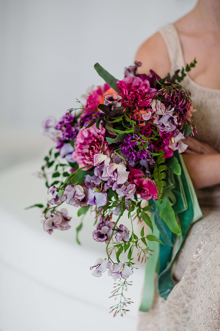 Cascading bridal bouquet with purple scabiosa, hellebores, sweet pea, Charlotte ranunculus, peach ranunculus, jasmine vine, fern, and vintage ribbons. By Cincinnati wedding florist Floral Verde.