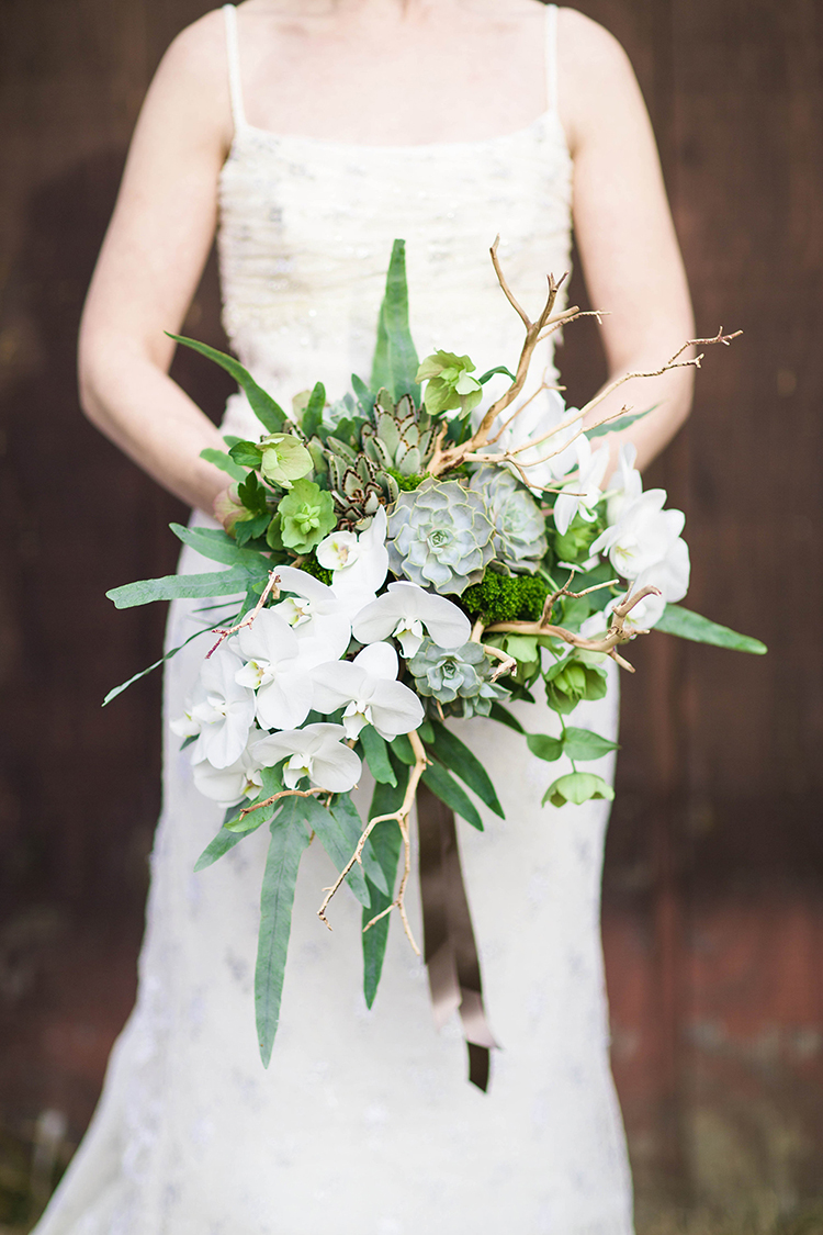 Cascading succulent bouquet with sandblasted manzanita branches, white phalaenopsis orchids, green hellebores, trachelium, ferns, and generous satin ribbon. By Cincinnati wedding florist Floral Verde.