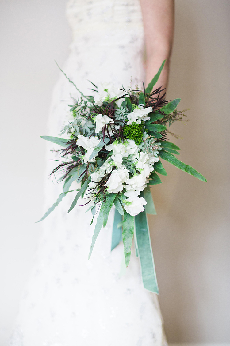 Cascading bridal bouquet with white sweet pea, agonis, feather acacia, Blue Star fern, green trachelium, and vintage grosgrain and velvet ribbons. By Cincinnati wedding florist Floral Verde.