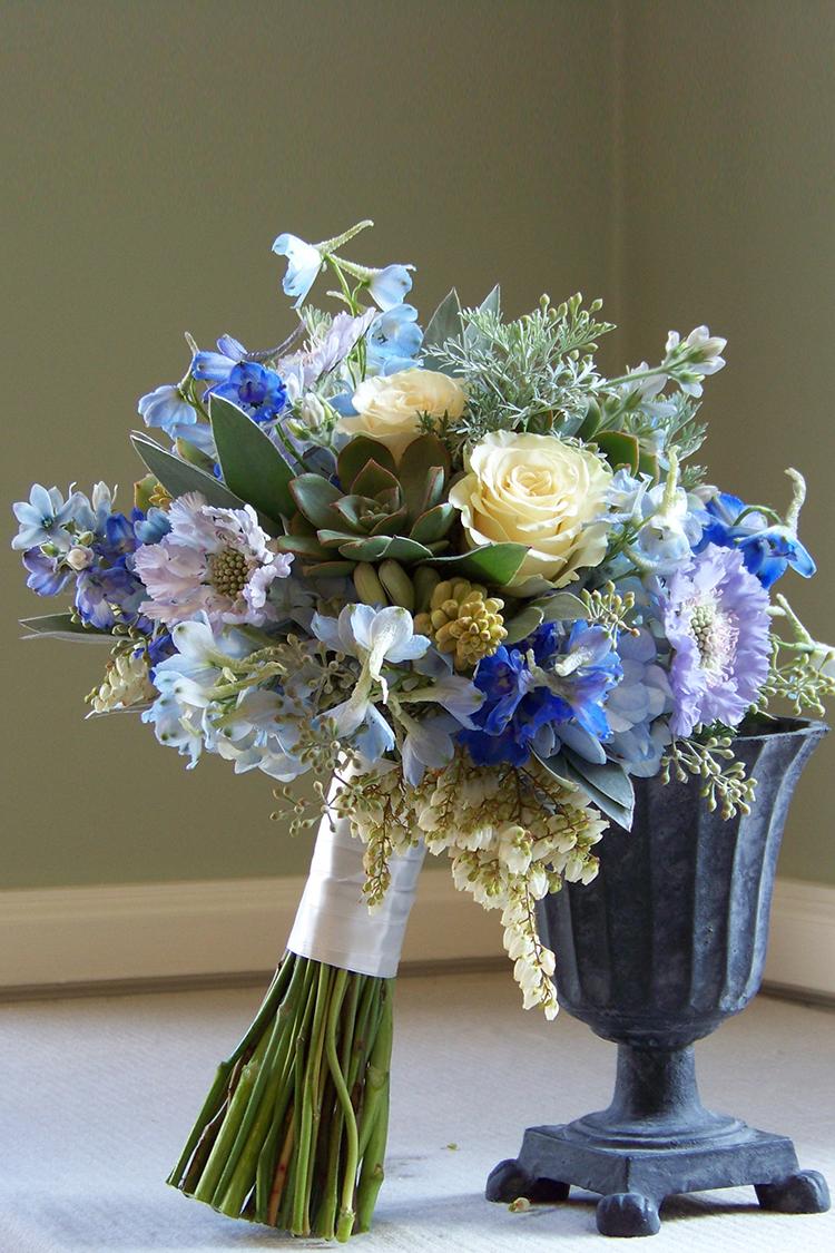 Bridal bouquet with delphinium, blue scabiosa, tweedia, hydrangea, pieris, tuberose, Cream Prophyta roses, eucalyptus, silver tree, wormwood and succulents. By Cincinnati wedding florist Floral Verde.