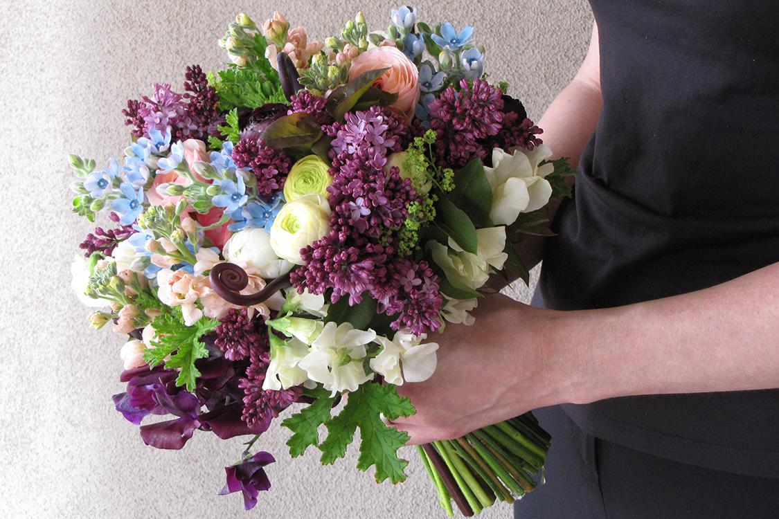 Spring bridal bouquet with uhule fern, purple sweet pea, ranunculus, lilacs, tweedia, scented geranium, alchemilla, ivory sweet pea and peach stock. By Cincinnati wedding florist Floral Verde LLC.