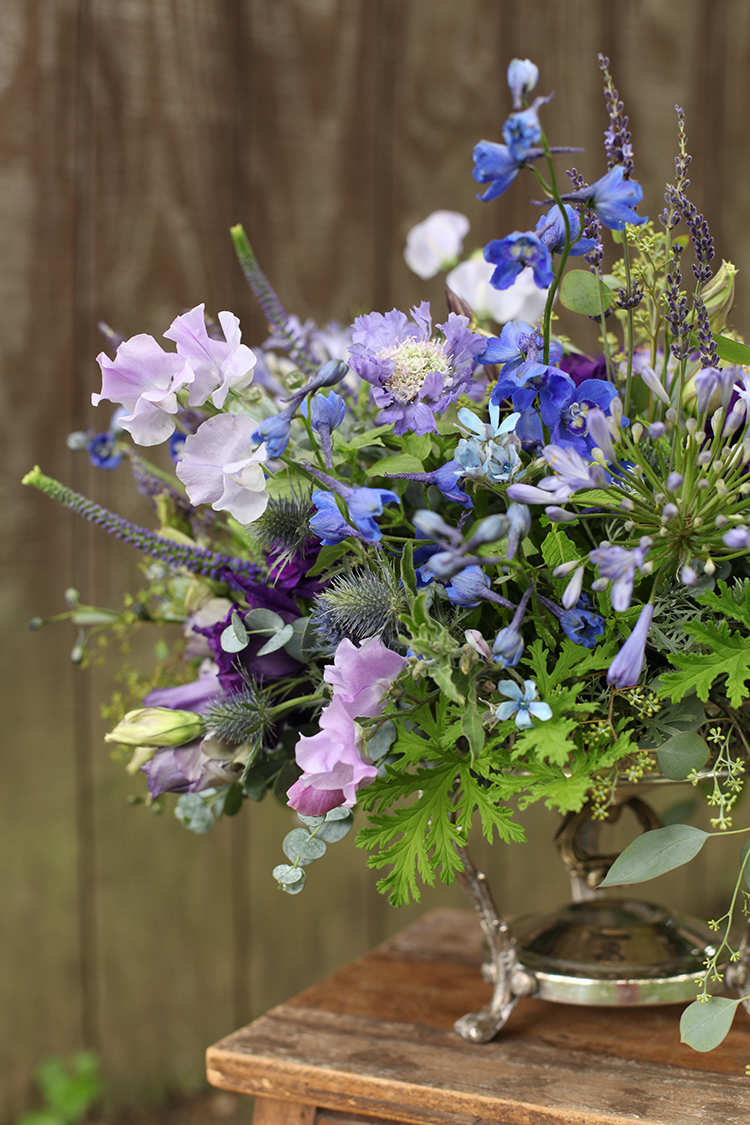 Garden centerpiece with purple lisianthus, lavender sweet pea, lavender, Sea Waltz delphinium, blue veronica, blue scabiosa, blue agapanthus, tweedia, gunnii eucalyptus, Artemisia 'Powis Castle', seeded eucalyptus, bunny tail grass, scented geranium, mint, and lemon basil in a vintage silver chafing dish, by Cincinnati wedding florist Floral Verde LLC.