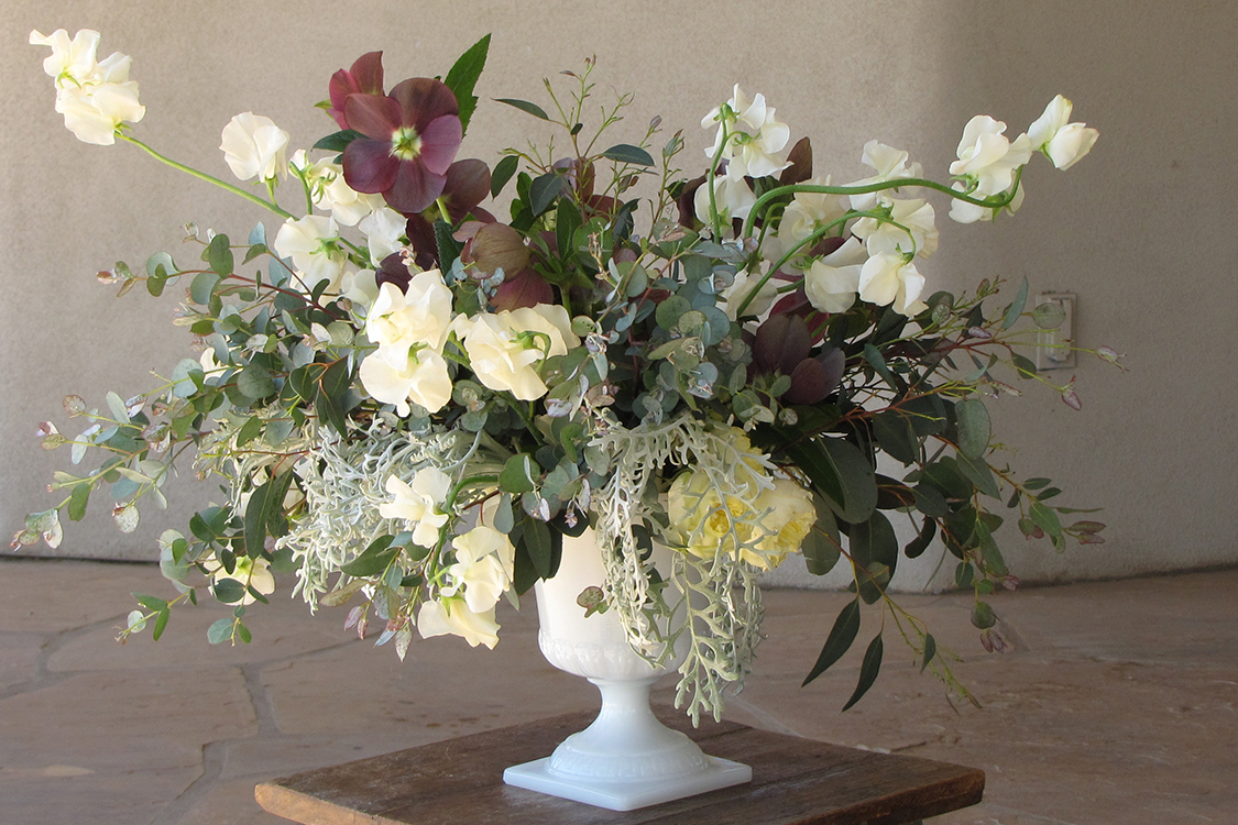 Garden centerpiece in a vintage milk glass urn by Cincinnati wedding florist Floral Verde LLC. Centerpiece contains antique purple hellebores, gunnii eucalyptus, dusty miller, Antique Romantica garden spray roses, and ivory Japanese sweet pea.