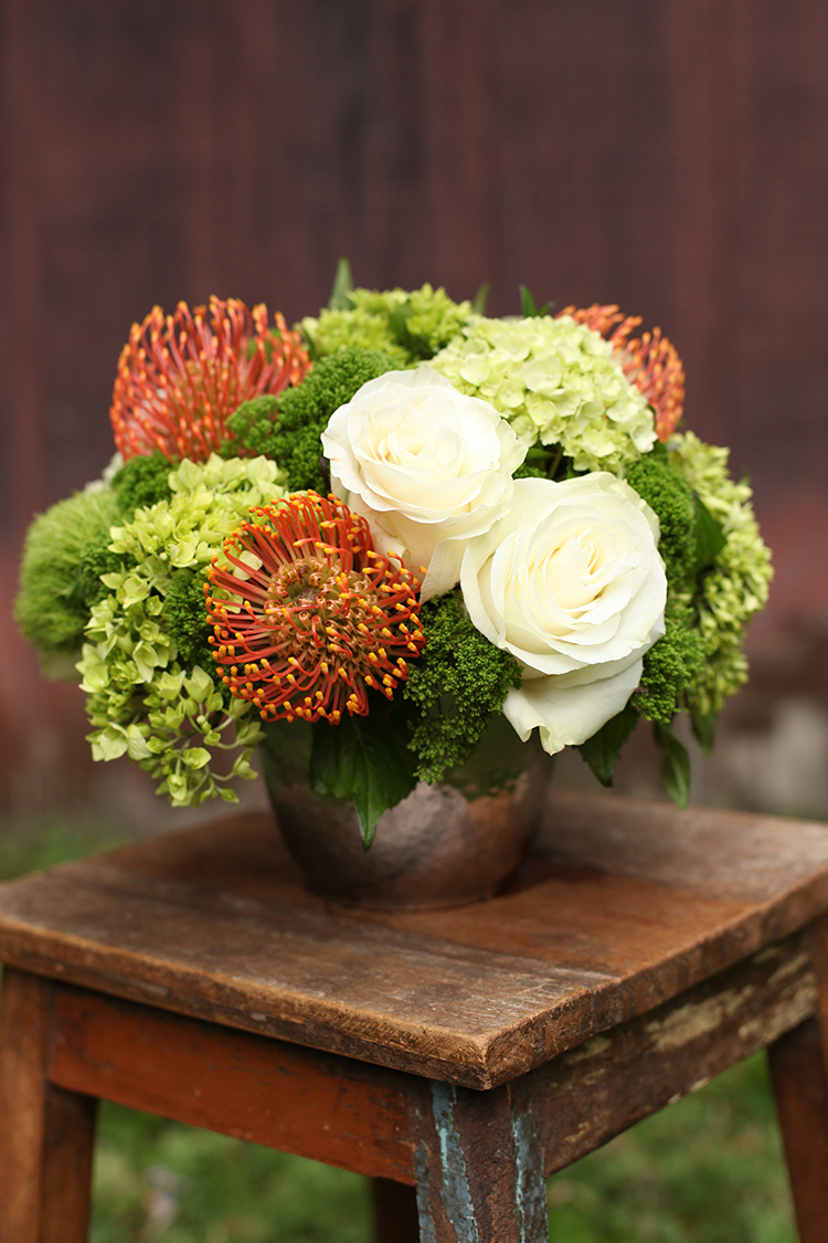 Centerpiece for Huntington Bank at the Cincinnati Zoo, by florist Floral Verde LLC in Cincinnati, Ohio.  Centerpiece contains orange pin cushion protea, Mondial roses, mini green hydrangea, Green Trick dianthus and Jade trachelium, in a platinum ceramic pot
