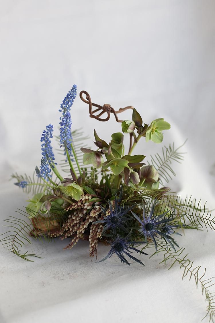 Woodland centerpiece with green hellebores, blue muscari, kiwi vine, eryngium, pieris, sea star fern and moss by Floral Verde LLC in Cincinnati, Ohio.