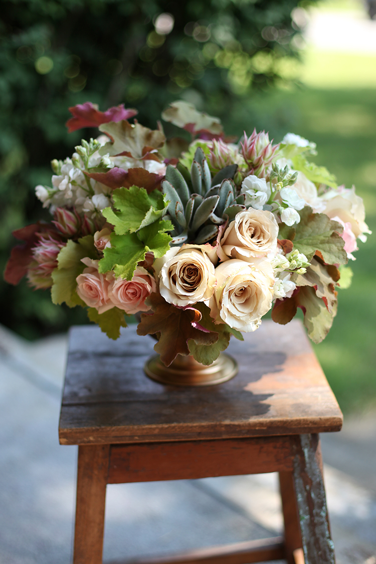 Centerpiece with Star Blush spray roses, Quicksand roses, blushing bride protea, white stock, caramel Heuchera, lime Heuchera and Kalanchoe tomentosa in a gold compote, by Cincinnati wedding florist Floral Verde LLC.