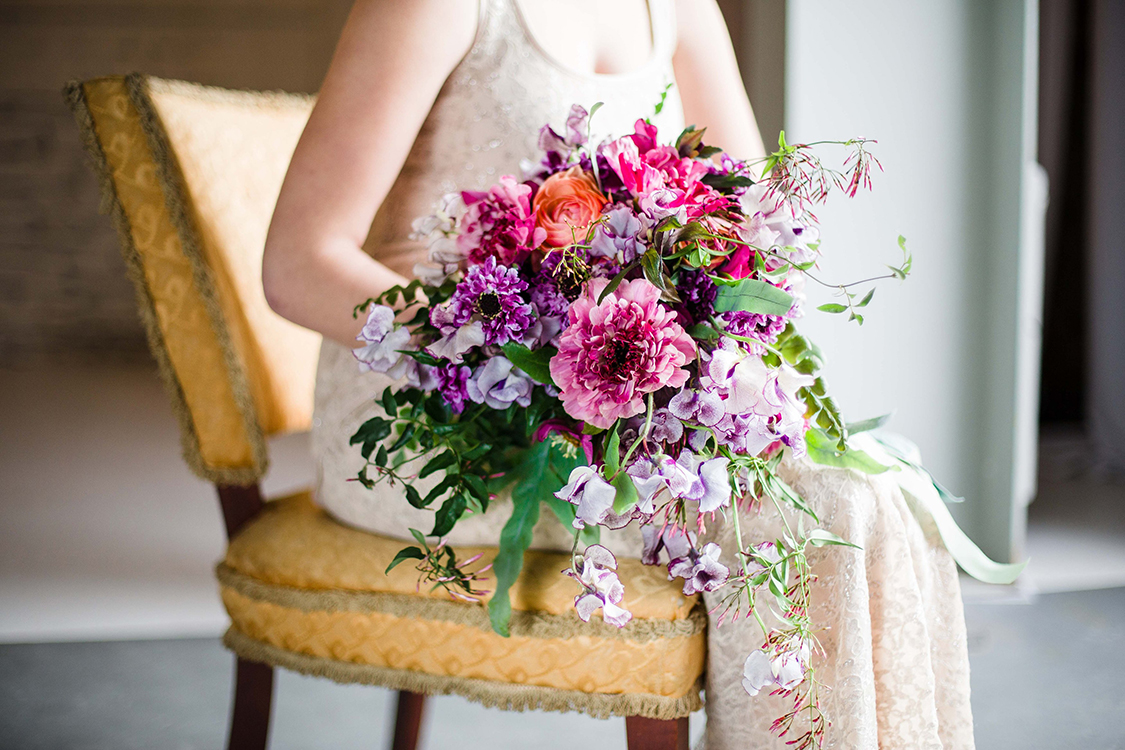 Cascading bridal bouquet with purple Japanese scabiosa, purple hellebores, Silvery Moon Japanese sweet pea, Charlotte ranunculus, peach ranunculus, jasmine vine and blue star fern, accented with vintage velvet and grosgrain cascading ribbons. Image by  Leah Barry Photography . Flowers by Cincinnati wedding florist Floral Verde LLC.