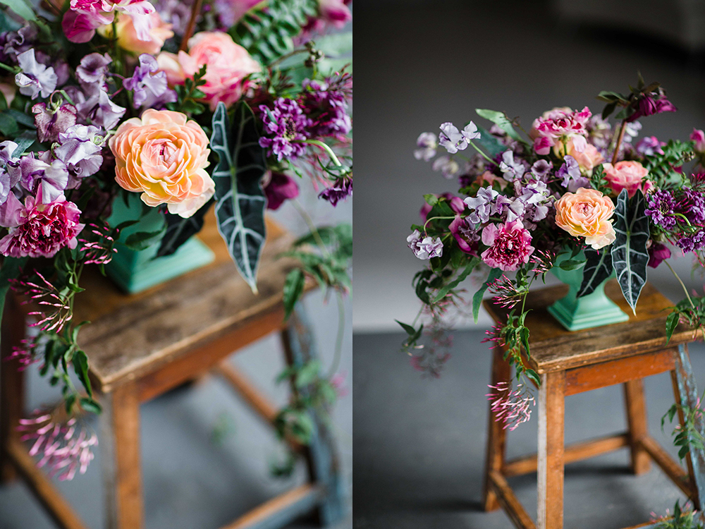 Overflowing centerpiece with purple Japanese scabiosa, purple hellebores, Silvery Moon Japanese sweet pea, Charlotte ranunculus, peach ranunculus, jasmine vine, blue star fern and Alocasia 'Polly', in a vintage mint footed bowl.  Images by  Leah Barry Photography . Flowers by Cincinnati wedding florist Floral Verde LLC.