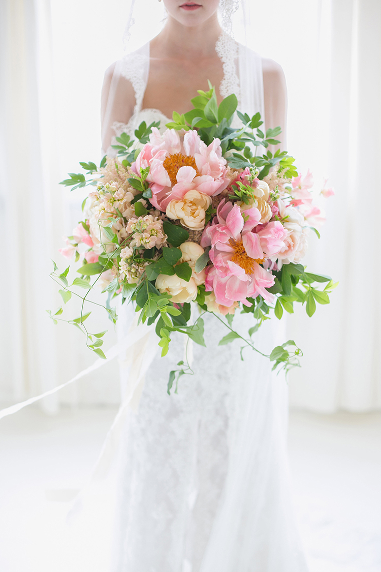 Bridal bouquet with Coral Charm peonies and garden roses. By Cincinnati wedding florist Floral Verde.