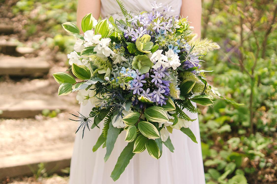 Asymmetric bouquet with white sweet pea, peonies, blue agapanthus, tweedia, eryngium, dusty miller, ferns, succulents, bunny grass, green helleborus and polygonatum. By Cincinnati florist Floral Verde