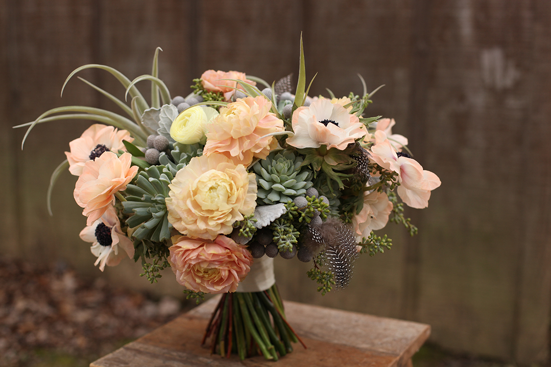Bridal bouquet by Cincinnati florist Floral Verde, including tillandsias, succulents, peach and ivory ranunculus, peach anemones, brunia, dusty miller, seeded eucalyptus and guinea fowl feathers.